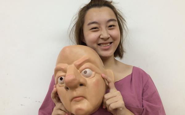 Smiling student holds mask