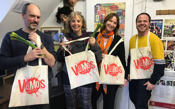 The Vamos Theatre Board holding tote bags