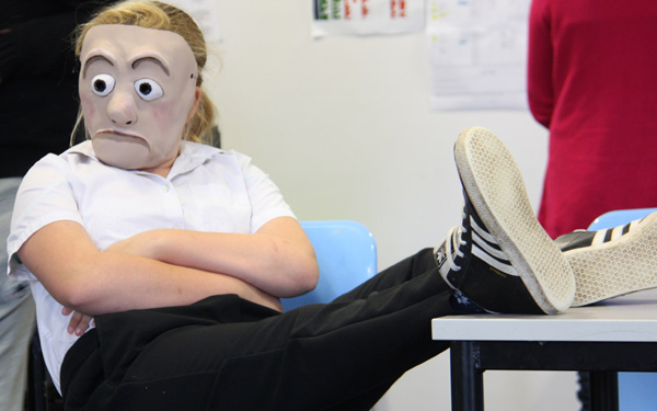 Mask character with feet on desk