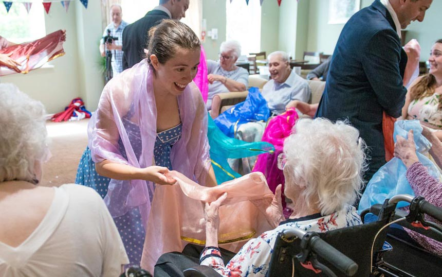 Performer holds hands with care home resident