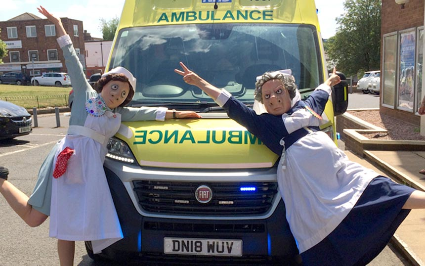 Two nurses in mask with an ambulance