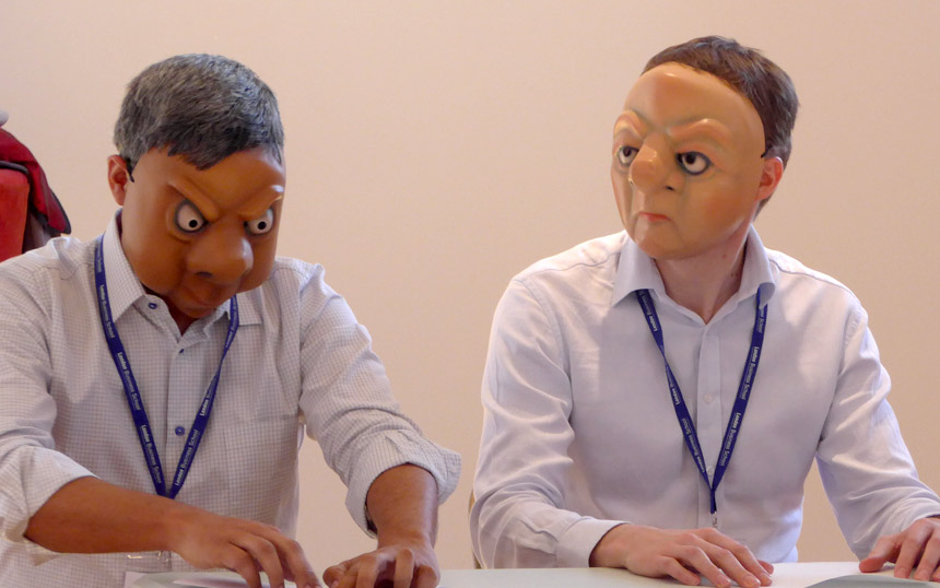 Two mask performers sitting at a desk