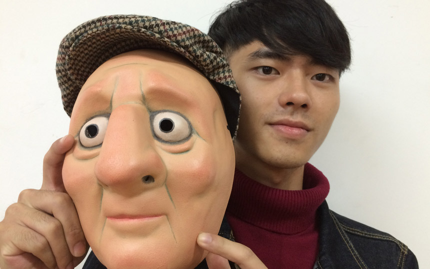 Actor holds up a character mask