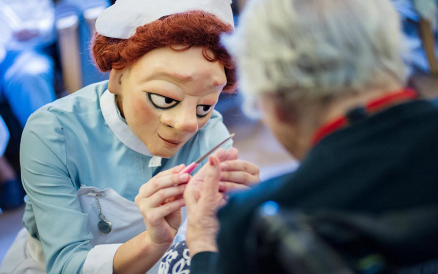 Mask character gives participant a manicure
