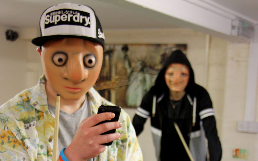 Boy in a mask texts on a phone