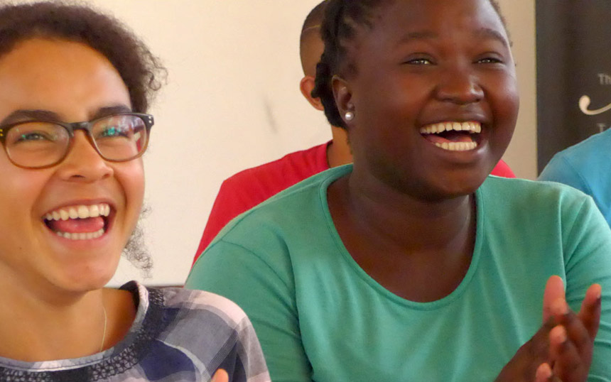 Two girls watching a workshop laughing
