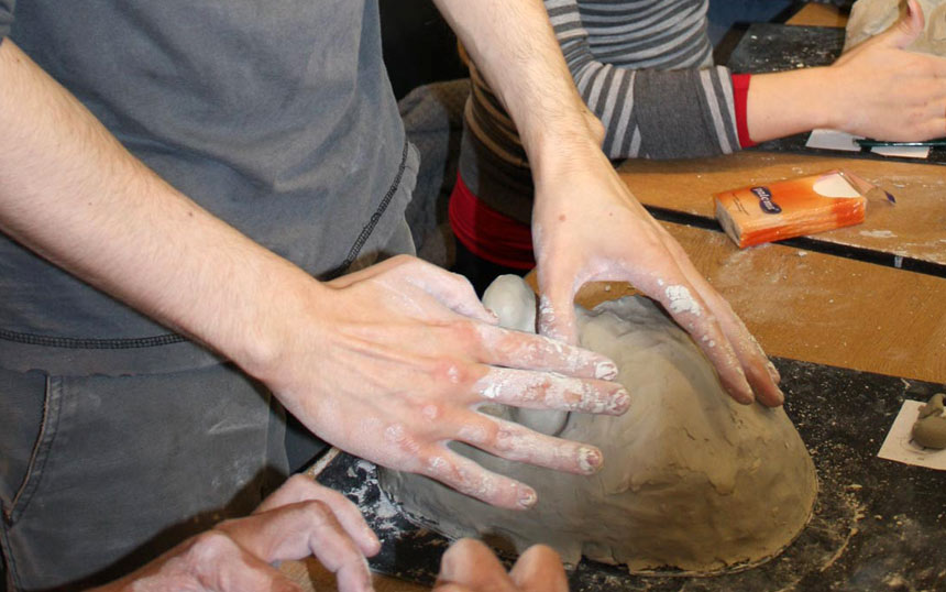 Hands mold clay for a mask